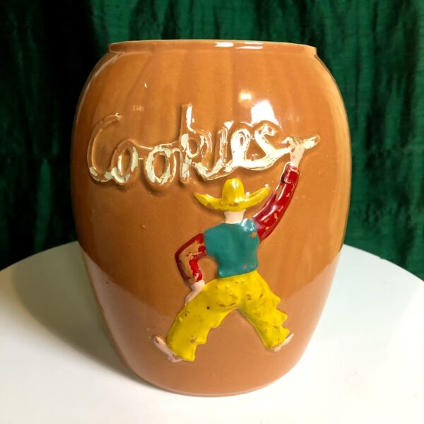"""Pictured, brown ceramic cookie jar with cowboy swinging a lasso spelling the word """"cookies"""". Available for event rental."""