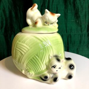 Pictured, green, ceramic cookie jar in the shape of a cotton ball with two kittens playing and making the handle. Available for event rentals