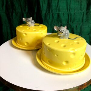 Pictured, pair of ceramic butter cover trays. Handles are shaped like a mouse and the covers are round blocks of yellow swiss cheese. Available for special event rental.