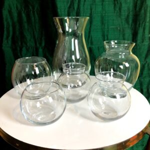 Pictured, assorted small glass vases. Four in a fish bowl style and two taller. Available for special event rental.