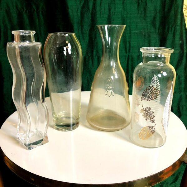 Pictured, set of four assorted tall glass vases with different shapes and patterns. Available for special event rental