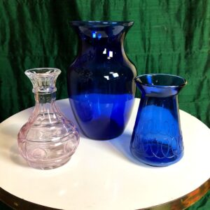 Pictured a set of three glass vases. One large and blue, one small and blue, and one small and purple tinted. Available for special event rental