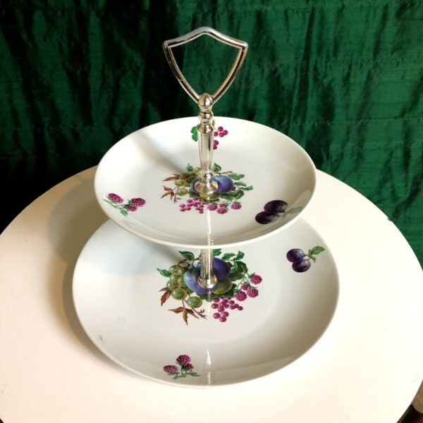 Pictured, tiered, white, ceramic dessert/snack tray with decorative grapes painted on it and a metal chrome handle. Available for special event rental