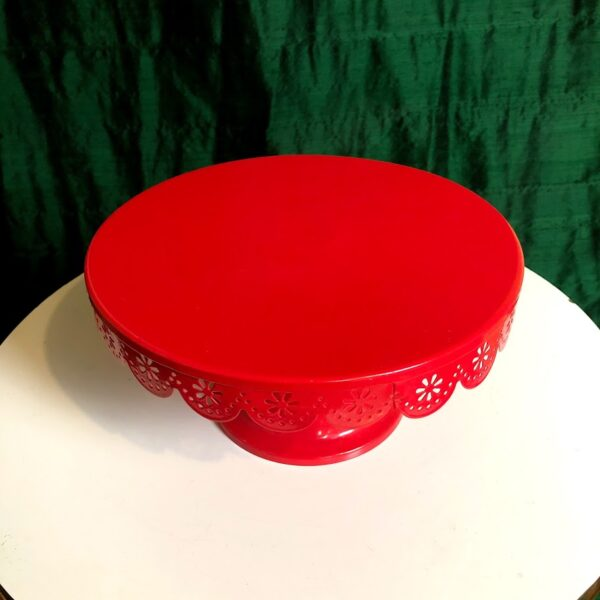Pictured, red metal cake stand with decorative patterning on the edge, available for special event rental