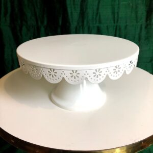 Pictured, white metal cake stand with decorative patterning on the edge, available for special event rental
