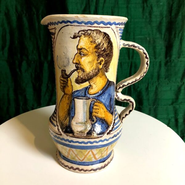 Pictured, front of a hand painted water pitcher with blue water colors and image of a man with a pipe and a ship on the ocean available for event rental