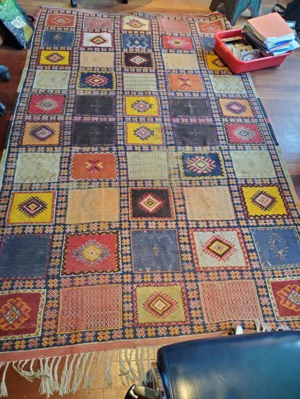 Pictured, Moroccan rug with multi-colored squares, among the vintage rental furniture from Catalyst Ranch