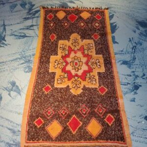 Pictured, small vintage brown rug with yellow flowers, among the vintage furniture of Catalyst Ranch