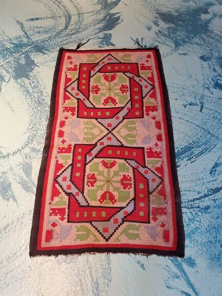 Pictured, red, green, and blue vintage Oriental rug, among the furniture of Catalyst Ranch