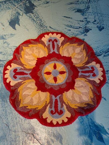 Pictured, round rug in red, blue & beige flower pattern, among the vintage furniture of Catalyst Ranch