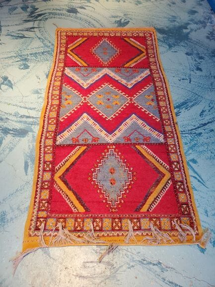 Pictured, red, blue & yellow small Moroccan rug, among the vintage furniture of Catalyst Ranch