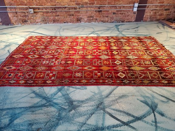 Pictured, red Moroccan rug with diamond and square pattern, among the vintage furniture of Catalyst Ranch