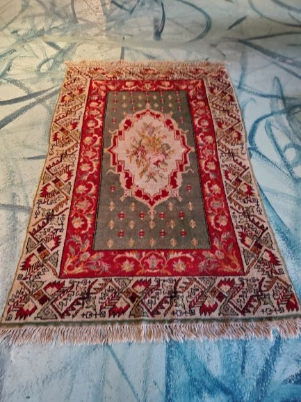 Pictured, green, red and beige Oriental rug, among the vintage furniture of Catalyst Ranch