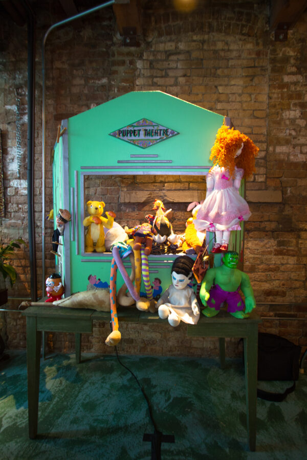 Pictured, teal wooden Puppet Theater with lots of figurines and dolls